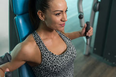 Healthy Young Woman Exercise Chest On Machine Stock Photos