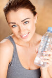 Healthy young woman holding a bottle of water. Smiling at home Royalty Free Stock Images