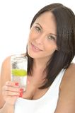 Healthy Young Woman Holding a Glass of Sparkling Water with Ice and Lime Royalty Free Stock Image