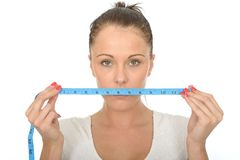 Healthy Young Woman Holding a Tape Measure Across Her Mouth Royalty Free Stock Photos