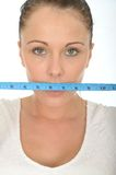 Healthy Young Woman Holding a Tape Measure Across Her Mouth Stock Photo