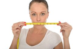 Healthy Young Woman Holding a Tape Measure Across Her Mouth Stock Image