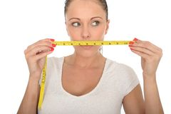 Healthy Young Woman Holding a Tape Measure Across Her Mouth Royalty Free Stock Image