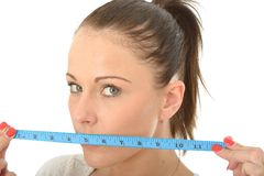 Healthy Young Woman Holding a Tape Measure Over Her Mouth Stock Photos