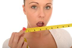 Healthy Young Woman Holding a Tape Measure with Shocked Expression. A DSLR royalty free image, of attractive healthy young woman, holding a stretched or pulled Royalty Free Stock Images