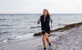 Healthy young woman jogging at the beach Royalty Free Stock Photography