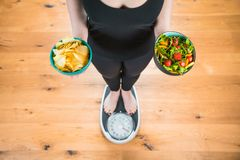 Healthy young woman looking at healthy and unhealthy food, trying to make the right choice.  stock images