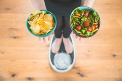 Healthy young woman looking at healthy and unhealthy food, trying to make the right choice.  stock photography