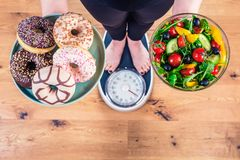 Healthy young woman looking at healthy and unhealthy food, trying to make the right choice.  royalty free stock images