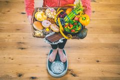 Healthy young woman looking at healthy and unhealthy food, trying to make the right choice.  royalty free stock photography
