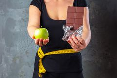Healthy young woman looking at healthy and unhealthy food, trying to make the right choice.  stock image