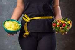 Healthy young woman looking at healthy and unhealthy food, trying to make the right choice.  stock photos