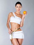 Healthy young woman with measuring tape and orange Stock Images