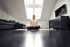 Healthy young woman meditating at home Royalty Free Stock Images