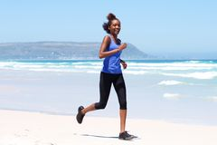 Healthy young woman running on the beach Royalty Free Stock Photography