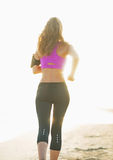 Healthy young woman running on beach. rear view Royalty Free Stock Photos