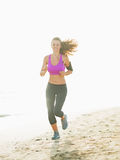 Healthy young woman running on beach Stock Images