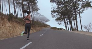 Healthy young woman running on country road stock footage
