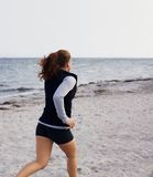 Healthy young woman running on seashore Stock Images