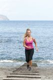 Healthy young woman running on thr beach Stock Photography