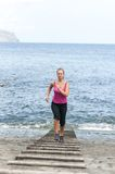 Healthy young woman running on thr beach Royalty Free Stock Images