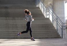 Healthy young woman running in urban environment stock photos
