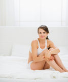 Healthy young woman sitting on bed Stock Images
