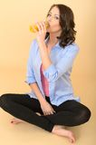 Healthy Young Woman Sitting On Floor Drinking Fresh Orange Juice Stock Image