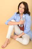 Healthy Young Woman Sitting on Floor Holding a Bottle of Still Mineral Water Stock Images