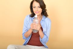 Healthy Young Woman Sitting on Floor Holding a Bottle of Still Mineral Water Royalty Free Stock Photo