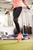 Healthy young woman skipping rope in a gym, crop Stock Photography