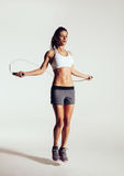 Healthy young woman skipping rope in studio Royalty Free Stock Images
