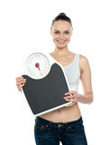 Healthy young woman with a weighing scale Royalty Free Stock Photos