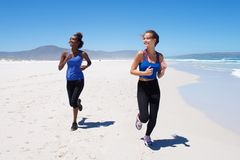 Healthy young women running along the beach Royalty Free Stock Photo