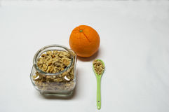 Healty food with bowel of cereals, spoon and orange Royalty Free Stock Photo