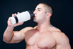 Healty life. The Perfect muscular man enjoying a bottle of water after exercise royalty free stock images