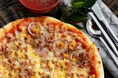 Healty pizza with tuna, onion and corn. A healty pizza with tuna, onion and corn served along some tomatos sauce and hot pepper Stock Image