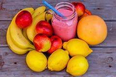 Healty rosa smoothie i den glass kruset och frukter på träbackgroun Royaltyfria Foton