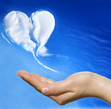 Heand and heart. Hand holding heart shaped cloud and blue sky Royalty Free Stock Images