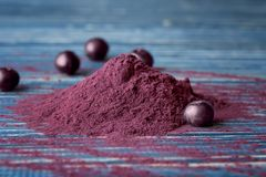 Heap of acai powder and berries on background. Heap of acai powder and berries on wooden background stock images