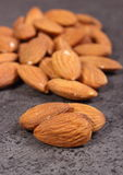 Heap of almonds on concrete structure Stock Images