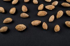 Almonds  in shell. Heap of almonds in shell isolated on black. Raw food ingredients Royalty Free Stock Photo