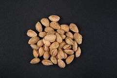 Almonds  in shell. Heap of almonds in shell isolated on black. Raw food ingredients Royalty Free Stock Images