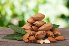 Heap of almonds in their skins and peeled with leaf isolated on white background Royalty Free Stock Image