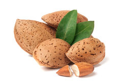 Heap of almonds in their skins and peeled with leaf isolated on white background Royalty Free Stock Images
