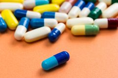 Heap of assorted colorful capsules on orange background. One blu. E pill is in front of the ohters Stock Images