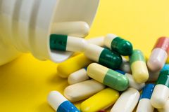 Heap of assorted colorful capsules on yellow table. Bottle spilling out tablets Royalty Free Stock Photos