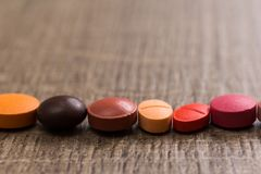 capsules on wooden table. Pills are making a line or path. Concept of way, course. royalty free stock photo