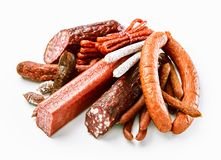 Heap of assorted dried spicy sausages on white. Heap of assorted seasoned dried spicy beef and pork sausages and salami on white suitable for advertising and Stock Photography