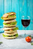 Heap of Bagels with salmon, vegetables, cream-cheese and glass of red wine on grey concrete background Royalty Free Stock Image